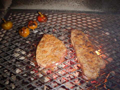 steaks cooking on precast outdoor fireplace
